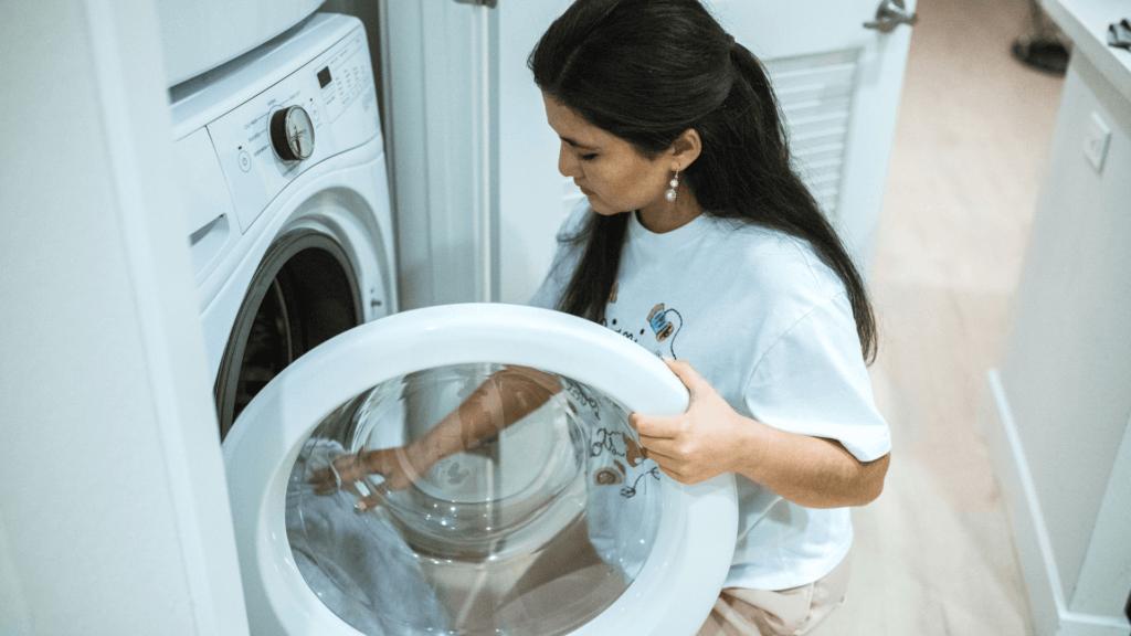 Sieviete ievieto apģērbu veļas mašīnā